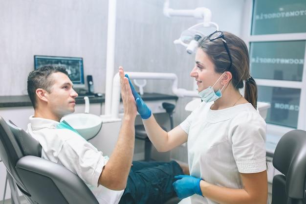 Retrato de um dentista fêmea e de um paciente masculino feliz novo em um consultório dentista. homem