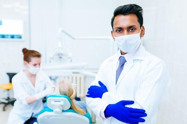 Retrato de um dentista masculino asiático seguro novo na clínica na frente do dentista do wfemale que verifica os dentes ao paciente. conceito de clínica dentária