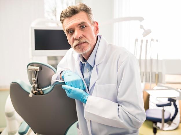 Retrato de um dentista sênior sorridente na clínica odontológica.