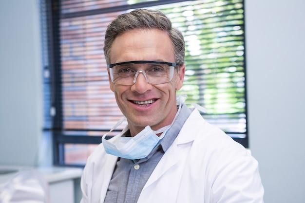 Retrato de um dentista sorridente em pé contra a janela