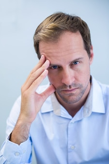 Retrato de um dentista tenso sentado com a mão na testa