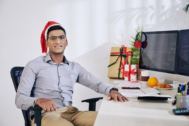 Retrato de um desenvolvedor de software indiano positivo com chapéu de papai noel sentado na mesa do escritório