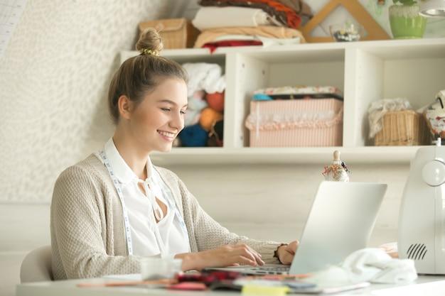 Retrato de um designer de pano de jovem mulher com laptop