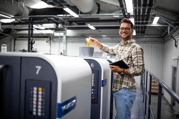 Retrato de um designer gráfico profissional sorridente ao lado de uma grande máquina de impressão offset