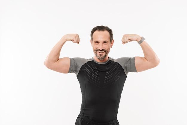 Retrato de um desportista maduro feliz flexionando os bíceps