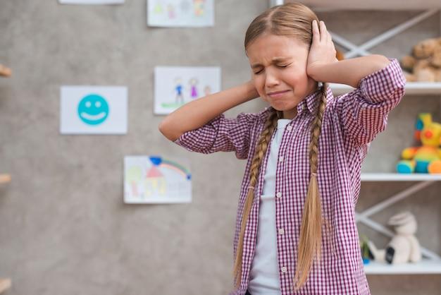 Retrato, de, um, distraught, menina, cobertura, dela, orelhas, com, duas mãos