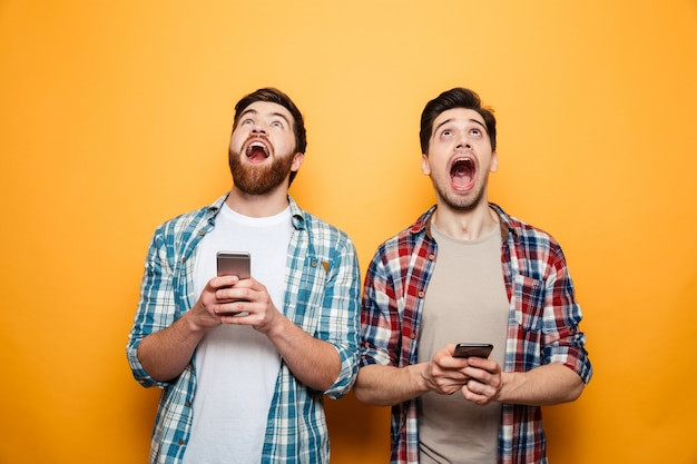 Retrato, de, um, dois, excitado, homens jovens, segurando, telefones móveis
