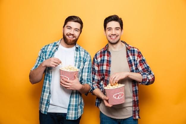 Retrato de um dois jovens alegres comendo pipoca