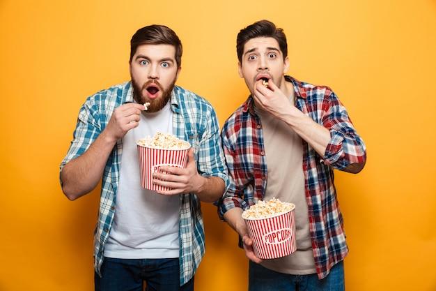 Retrato de um dois jovens assustados comendo pipoca