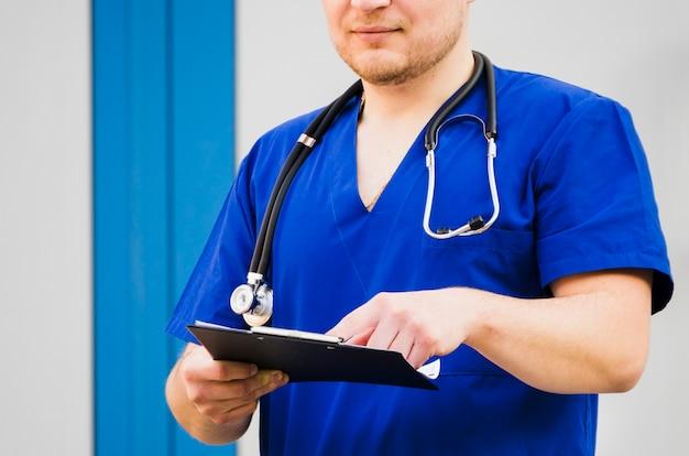 Retrato, de, um, doutor masculino, com, estetoscópio, ao redor, pescoço, examinando, a, relatório médico