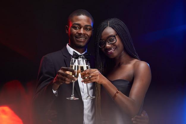 Retrato de um elegante casal afro-americano tilintando taças de champanhe enquanto posava em uma festa no escuro