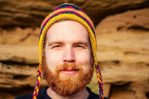 Retrato de um elegante turista ruivo ruivo com um chapéu colorido feito de lã de iaque do nepal