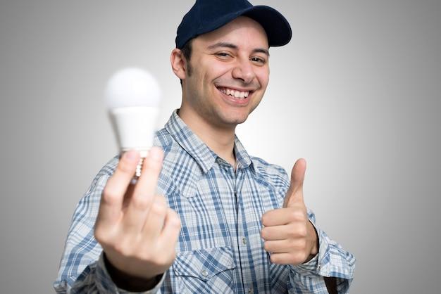 Retrato, de, um, eletricista, segurando, um, energy-saving, lightbulb