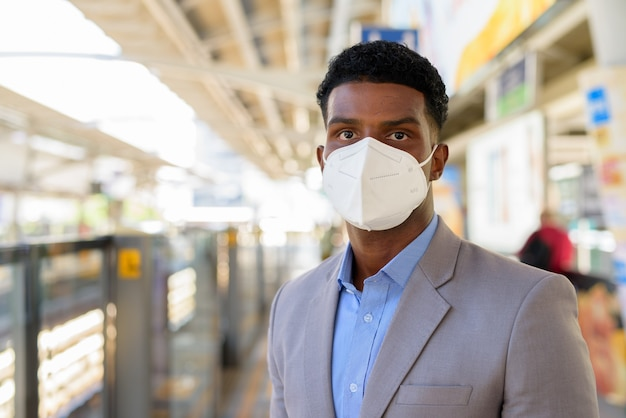 Retrato de um empresário africano na plataforma da estação ferroviária usando máscara facial