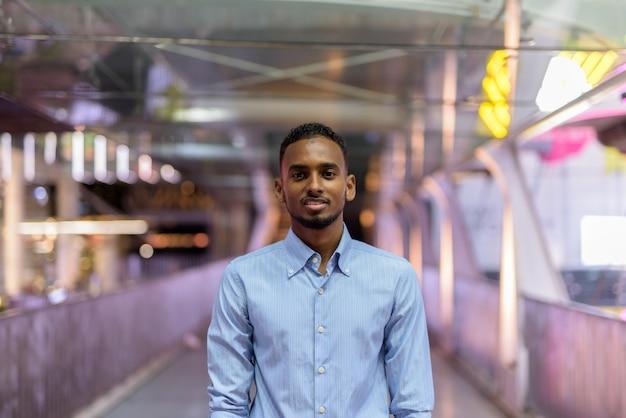 Retrato de um empresário africano negro bonito ao ar livre na cidade à noite em pé na ponte horizontal tiro horizontal