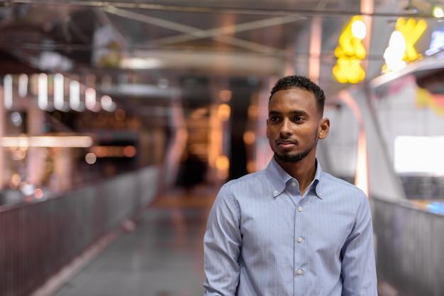 Retrato de um empresário africano negro bonito ao ar livre na cidade à noite, em pé na ponte para pedestres, pensando em tiro horizontal