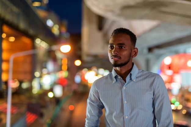 Retrato de um empresário africano negro bonito ao ar livre na cidade à noite, sorrindo e pensando na horizontal.
