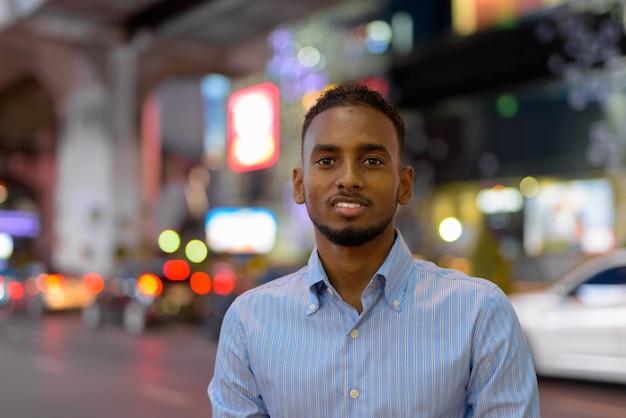 Retrato de um empresário africano negro bonito ao ar livre na cidade à noite, sorrindo horizontalmente.