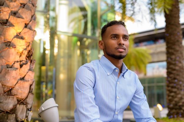 Retrato de um empresário africano negro bonito ao ar livre na cidade durante o verão, sentado e pensando na horizontal.
