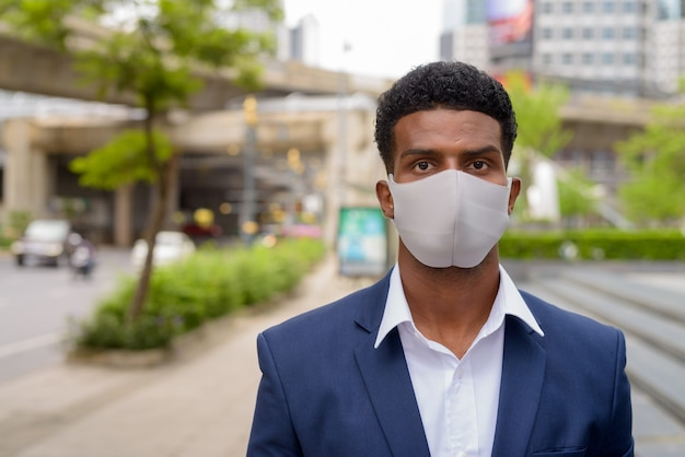 Retrato de um empresário africano usando máscara facial ao ar livre, plano horizontal
