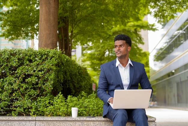 Retrato de um empresário africano usando um computador laptop ao ar livre no parque da cidade enquanto está sentado e pensando, plano horizontal