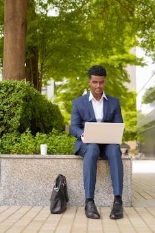 Retrato de um empresário africano usando um computador laptop ao ar livre no parque da cidade enquanto está sentado, foto vertical