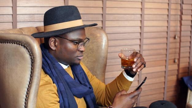 Retrato de um empresário afro-americano pensativo com smartphones na mão, um chefe de pele escura sentado em uma cadeira, móveis marrons