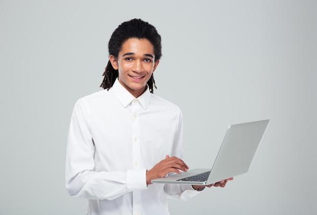 Retrato de um empresário afro-americano sorridente usando laptop e olhando para a frente, sobre uma parede cinza