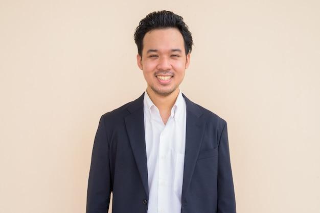 Retrato de um empresário asiático feliz vestindo terno contra um fundo liso