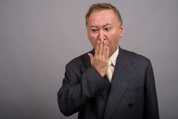 Retrato de um empresário asiático maduro contra um fundo cinza