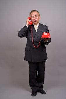 Retrato de um empresário asiático maduro contra uma parede cinza