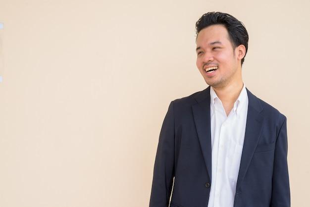 Retrato de um empresário asiático vestindo terno contra um fundo liso, sorrindo e pensando