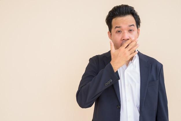 Retrato de um empresário asiático vestindo um terno contra um fundo liso, parecendo chocado