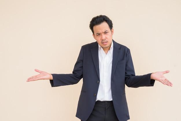 Retrato de um empresário asiático vestindo um terno contra um fundo simples e parecendo zangado e confuso