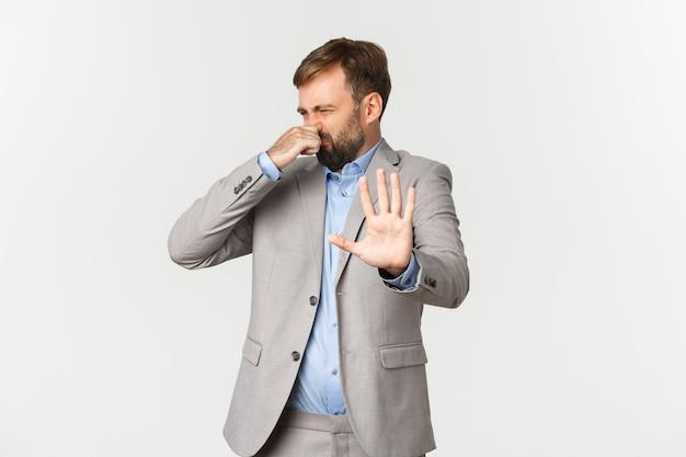 Retrato de um empresário barbudo enojado, rejeitando algo com um cheiro horrível