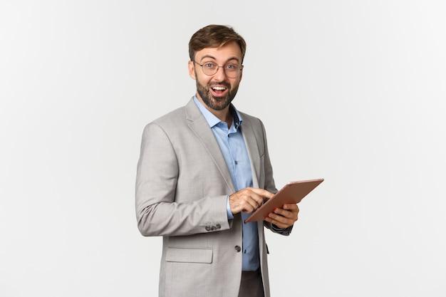 Retrato de um empresário barbudo feliz e surpreso de terno cinza e óculos, segurando o tablet digital.