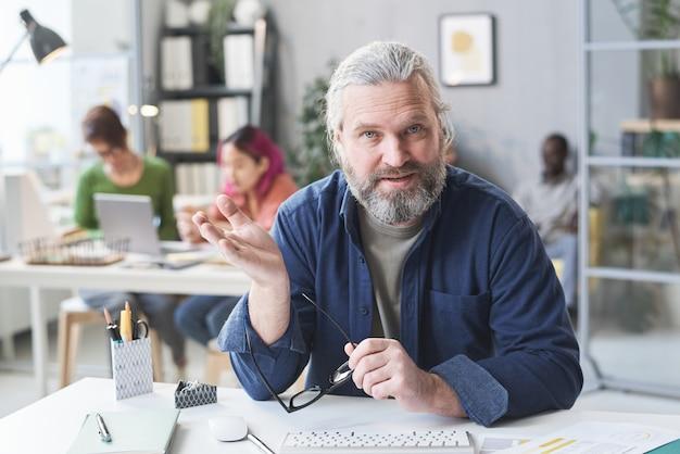 Retrato de um empresário barbudo maduro sentado em seu local de trabalho, gesticulando e falando