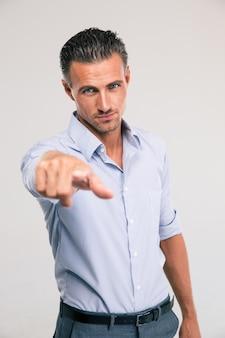 Retrato de um empresário bonitão apontando o dedo para a câmera no espaço cinza