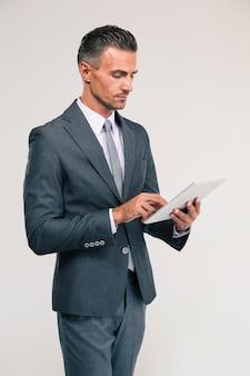 Retrato de um empresário bonitão usando um computador tablet isolado