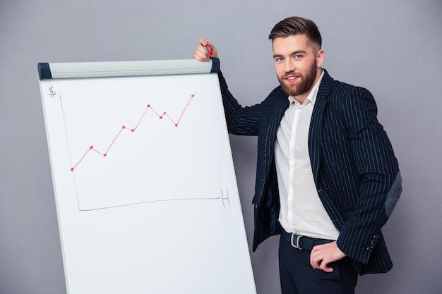 Retrato de um empresário bonito apresentando algo a bordo sobre uma parede cinza