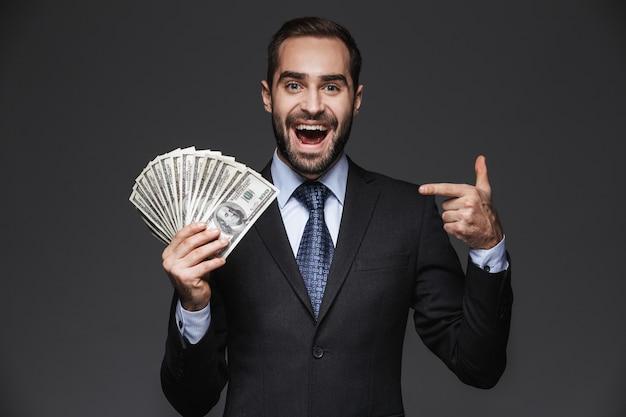 Retrato de um empresário bonito e confiante vestindo terno isolado, mostrando notas de dinheiro