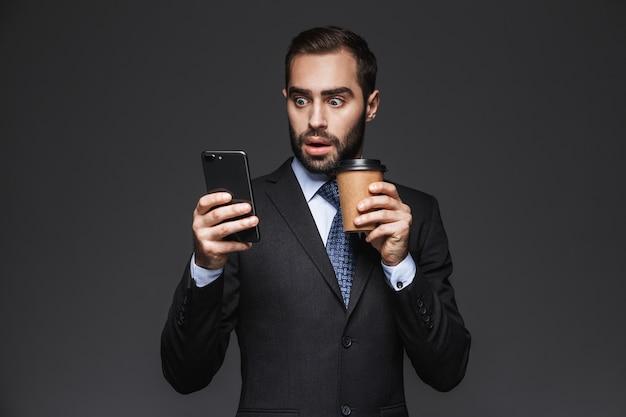 Retrato de um empresário bonito e confiante vestindo um terno de pé isolado, segurando uma xícara de café para viagem, usando um telefone celular