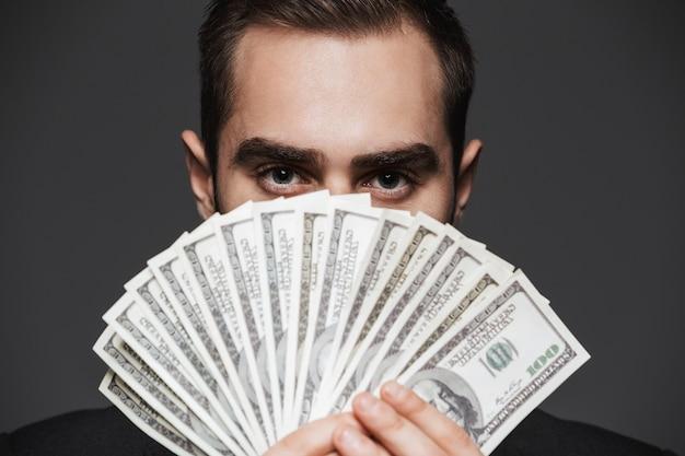 Retrato de um empresário bonito e confiante vestindo um terno, isolado, mostrando notas de dinheiro
