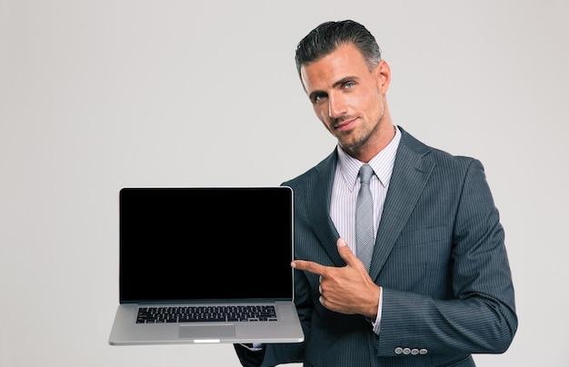 Retrato de um empresário bonito mostrando a tela do laptop em branco isolada