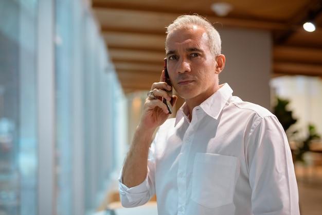 Retrato de um empresário bonito na cafeteria falando no celular horizontal tiro