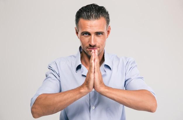 Retrato de um empresário bonito rezando isolado