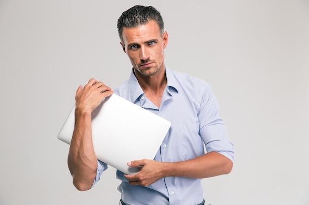 Retrato de um empresário bonito segurando laptop isolado. olhando para a câmera