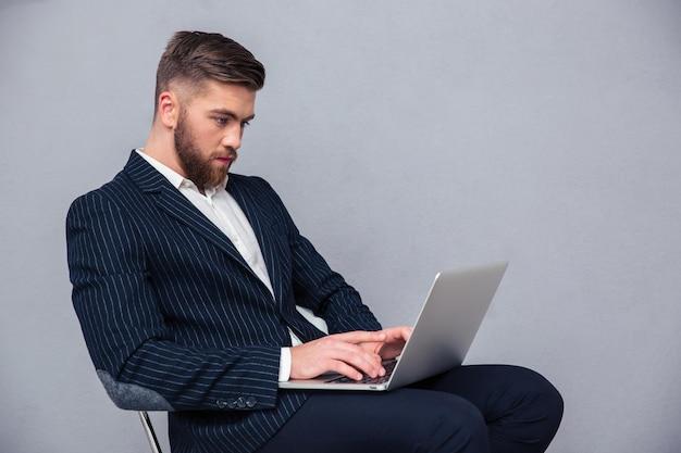 Retrato de um empresário bonito sentado na cadeira do escritório e usando o laptop sobre uma parede cinza
