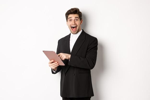 Retrato de um empresário bonito surpreso, vestindo um terno da moda, mostrando algo legal no tablet digital, em pé contra um fundo branco
