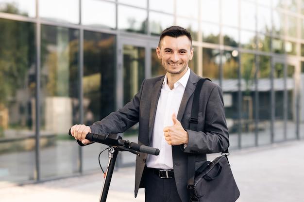 Retrato de um empresário caucasiano apoiado na scooter elétrica e olhando para o homem stylysh da câmera